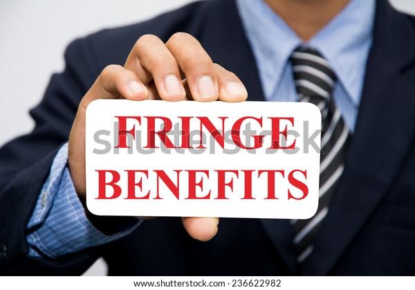 Businessman hand holding FRINGE BENEFITS concept
