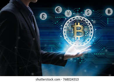 Businessman hand holding global network using Currencies sign symbol interface of Bitcoin Fintech, virtual currency blockchain technology concept, Investment Financial Technology Concept.