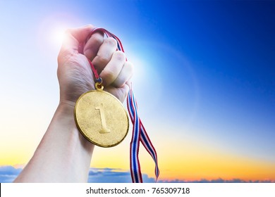 Businessman hand holding golden coin medal.