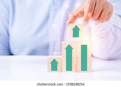 Businessman hand holding green arrow graph wood block with technology business concept, creative idea graph business development to growth profit and success for target concept.