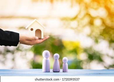 Empresario que sostiene la casa con la presentación a la familia puesta en la madera en el bokeh de la naturaleza en el parque público, préstamo de negocios para comprar casa o propiedad inmobiliaria en el futuro concepto.