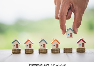 The businessman hand holding the house is about to put on the coin. Real estate concept, mortgage, investment, save money or investment for future homes.House models and coins.