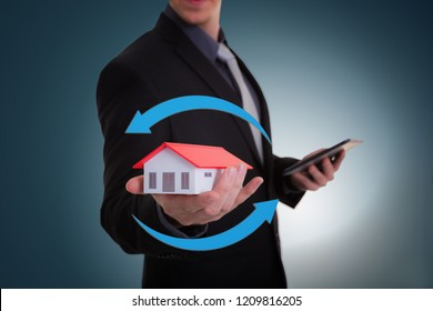 Businessman hand holding house representing home ownership and the Real Estate business with tablet.Refinance concept and Business investment growth concept.