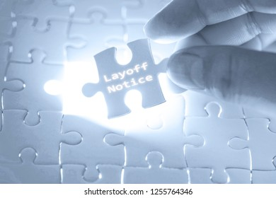 Businessman hand holding a jigsaw puzzle with layoff notice word. Business concept.
