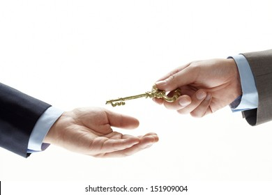 businessman hand holding a key and handing it over to another man. Hands and key on white background.