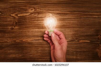Businessman hand holding light bulb. Success, creativity and new idea concept