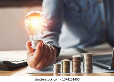businessman hand holding lightbulb with saving money in office. concept accounting and energy