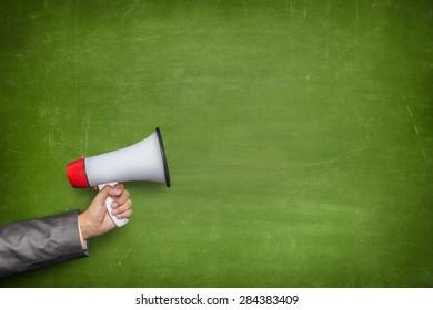 Businessman hand holding megaphone on front of vintage full frame green blank blackboard no frame