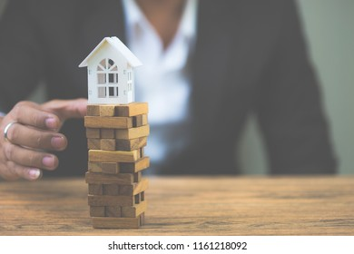 Businessman hand holding model white house on wood block. Investment risk and uncertainty in the real estate housing market. Property investment and house mortgage financial concept. with copy space