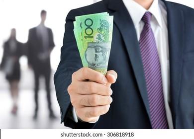 Businessman hand holding money, Australian dollar (AUD) banknotes