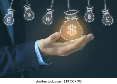 Businessman hand holding money bag with hologram on dark background, currency for investment and business concept