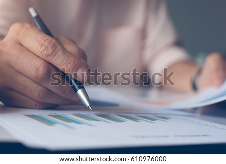 Businessman hand holding pen and working with business data strategy as concept, selective focus