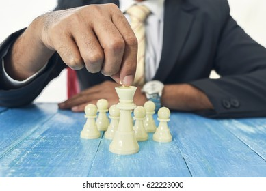 Businessman hand holding Queen with his pawn on the table. Leadership concept