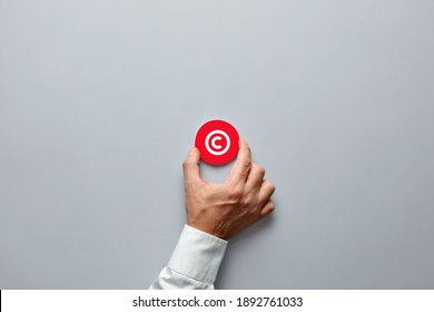 Businessman hand holding a red badge with copyright symbol. Property rights and brand patent protection in business concept.