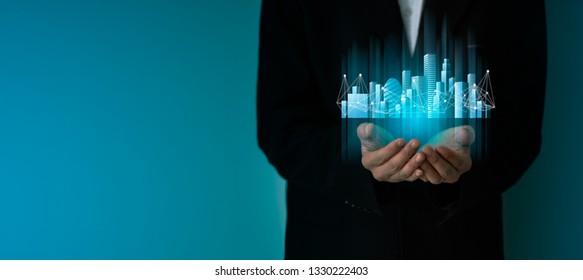 businessman hand holding a Smart city with smart services and icons, internet of things, networks and conection concept.