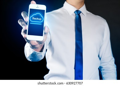 Businessman hand holding smart phone with Cloud Backup concept