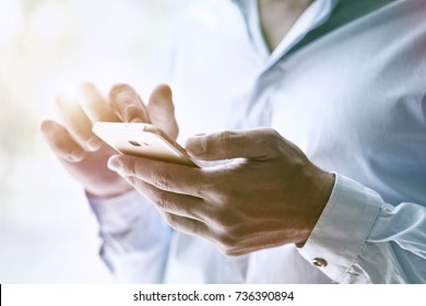 businessman hand holding smart phone typing with finger