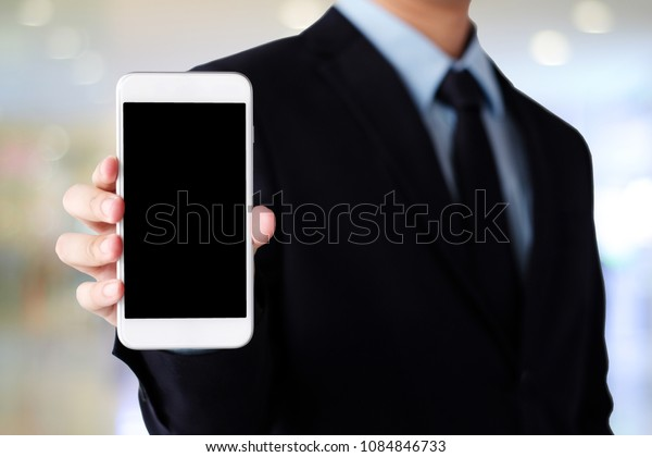 Businessman hand holding smartphone with blank on screen display over blur background, business people and technology display montage, mock up, template, background