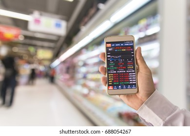 Businessman hand holding smartphone and Stock data information showing on screen with blurry modern trade in background.