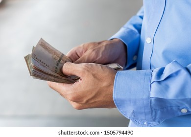 Businessman hand holding Thai Baht banknote stack. business, money, investment , finance and payment concepts