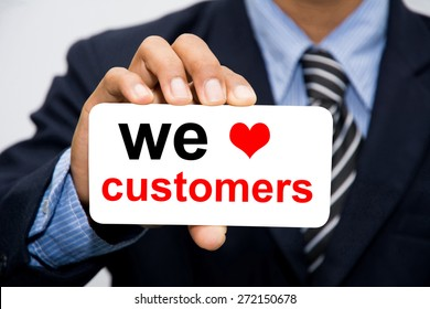 Businessman hand holding we love customers concept