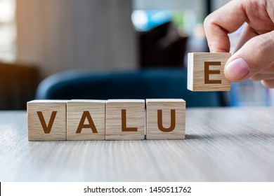 Businessman hand holding wooden cube block with Value business word on table background. Mission, Vision and core values concept
