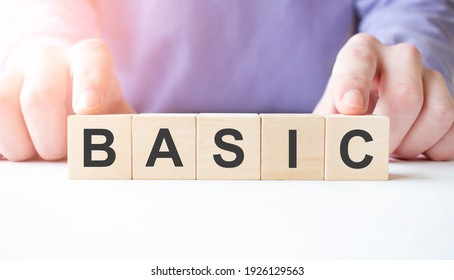 Businessman hand holding wooden cube block with BASIC business word on table background. Mission, Vision and core values concept