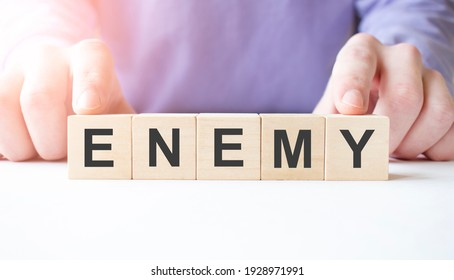 Businessman hand holding wooden cube block with ENEMY business word on table background. Mission, Vision and core values concept