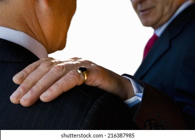 Businessman with hand on shoulder of colleague, close-up, cut out