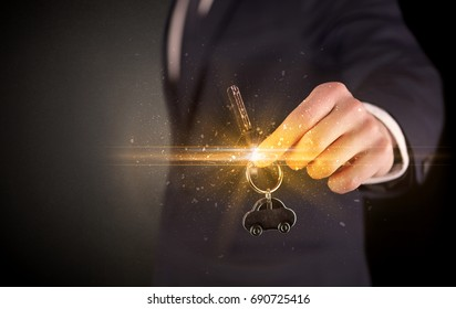 Businessman hand  over shiny keys in dark suit with dark background