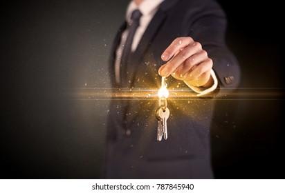 Businessman hand  over shiny keys in dark suit with dark background