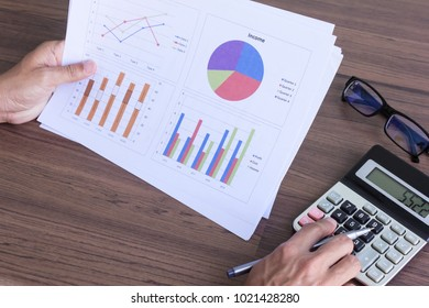 businessman hand with paperwork and calculator