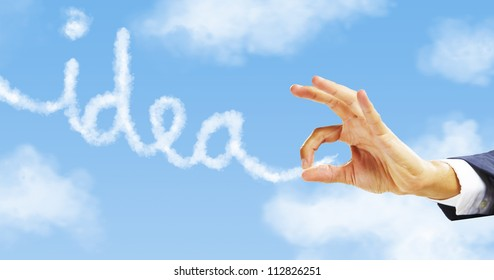 businessman hand pinching idea word. Hand taking clouds with sky background