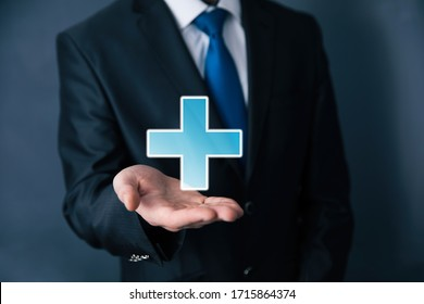 Businessman hand plus sign in screen on dark background