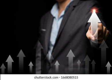 Businessman hand point to up or increase arrow black background. It is symbol of business investment growth concept.