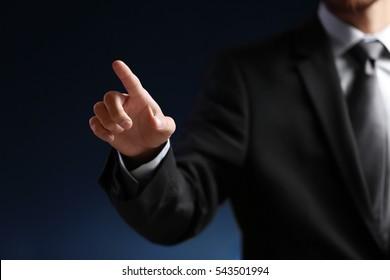 Businessman hand pointing, dark background