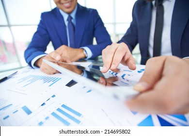 Businessman hand pointing at document in touchpad during explanation of data at meeting