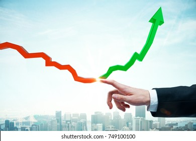 Businessman hand pointing at downward arrow and turning into a green rising one on light city background. Financial growth concept