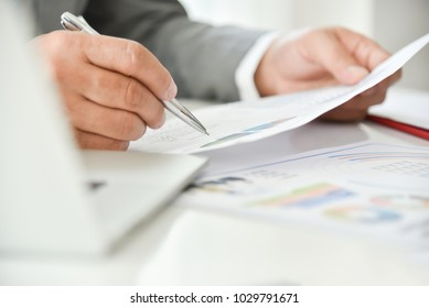 Businessman hand is pointing on business chart or graph documents with a pen.