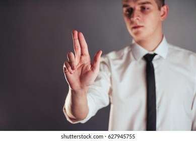 Businessman hand pointing on empty space on black background in the studio