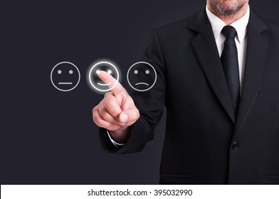 Businessman hand pointing the smiley face icon from screen as positive feedback concept against black background