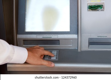 Businessman hand pressing a key in the keypad of a cash machine, outdoors.