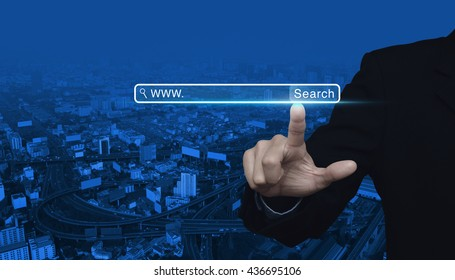 Businessman hand pressing search www button over city tower with highway background, Searching system and internet concept