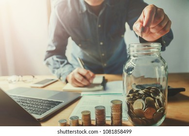 businessman hand puting coins into jug glass. saving money concept