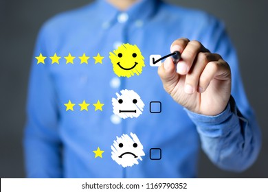 Businessman hand putting check mark a checkbox on happy face icon and five star rating. Customer service experience and satisfaction survey concept