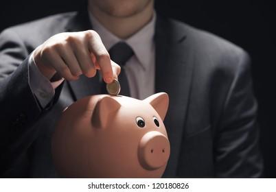 Businessman hand putting coin into a piggy bank