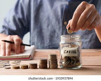 Businessman hand putting coins in glass jar. Concept of saving money, financial planning, investment, growth management, business, financial.