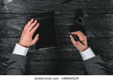 Businessman hand with a quill pen and black cover book on the black wooden table background.