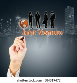 Businessman hand showing JOINT VENTURE concept with business people icon on virtual screen