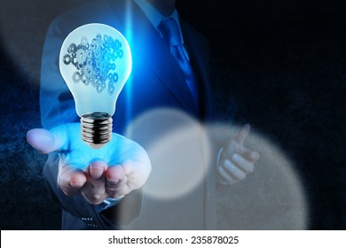 businessman hand showing light bulb with gears as concept